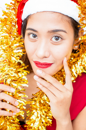 Close-up of smiling woman in Santa hat and tinsel