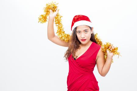 Flirty woman posing in Santa hat with tinsel