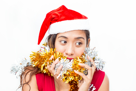 Portrait of pensive woman in Santa hat and tinsel Stock Photo