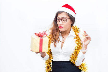 professional flute: Surprised woman in Santa hat holding gift box