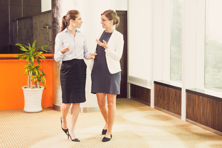 Business Women Chatting and Walking in Office Hall Stock Photo
