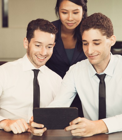 Smiling Business People Using Tablet in Office