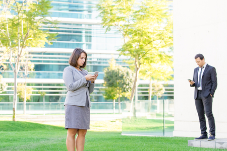 Business People Texting on Smartphones Outdoors