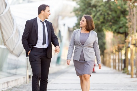 Two Happy Business Colleagues Walking on Street Stock Photo
