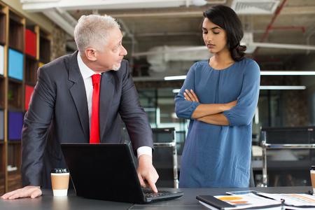 Hombre de negocios serio que muestra la presentación en la computadora portátil Foto de archivo - 88645460