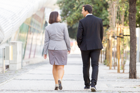 Back View of Two Partners Walking on Street