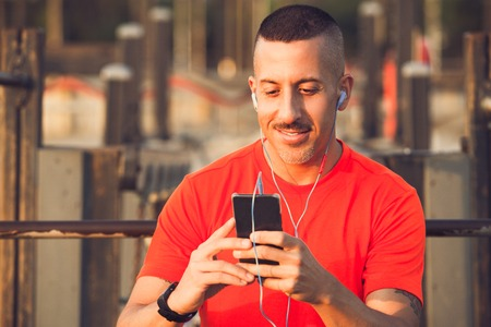 Smiling athlete downloading music to smartphone Stock Photo
