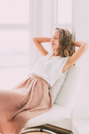Beautiful Woman Dozing on Chair on Loggia Stock Photo