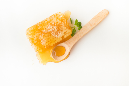 Honeycomb with herb and wooden spoon