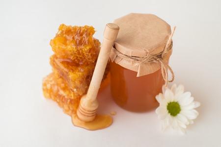 Honeycombs, honey jar, flower and dipper Stock Photo