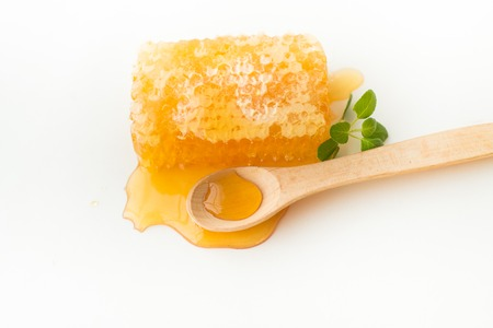 Close-up of honeycomb with herb and wooden spoon