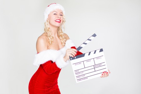 Happy woman in Santa costume with clapperboard Stockfoto