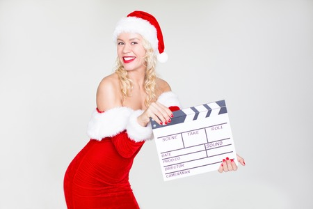 Female Santa holding clapperboard and smiling