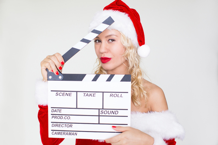 Flirty woman in Santa costume with clapperboard Stock Photo