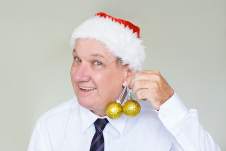 Smiling businessman holding baubles as earring Stock Photo