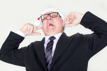 Furious businessman covering ears and screaming
