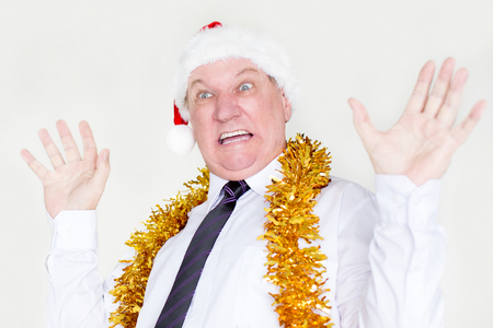 Scared businessman in Santa hat raising hands