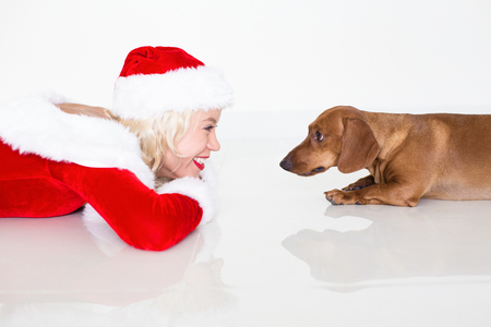 Closeup of Woman in Santa Dress Smiling at Dog Stock Photo