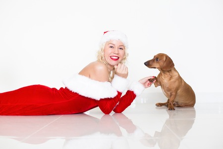 Dog Giving Paw to Happy Woman in Santa Costume Stock Photo