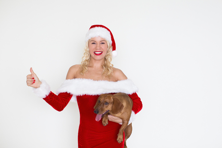 Happy Woman in Santa Hat with Dog Showing Thumb Up