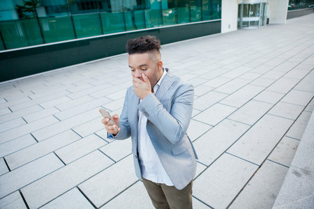 Portrait of young astounded businessman standing outside, closing his mouth with hand, holding smartphone and looking at screen. Man shocked with news. Good or bad news concept Фото со стока