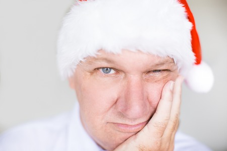 Closeup of Bored Middle-aged Man in Santa Hat