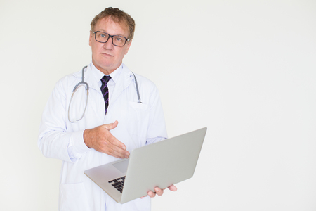Serious Mature Doctor Pointing at Laptop Computer
