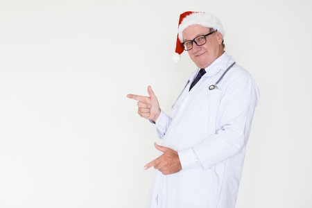 Smiling Mature Doctor in Santa Hat Pointing Aside