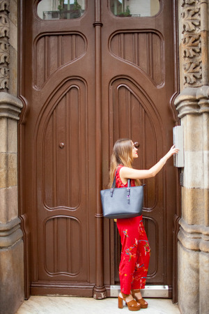 Pretty lady with bag ringing buzzer and standing against big door. Serious stylish young woman visiting friend and coming as guest. Intercom concept