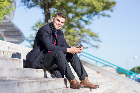 Happy businessman using mobile phone on stairs Stock Photo
