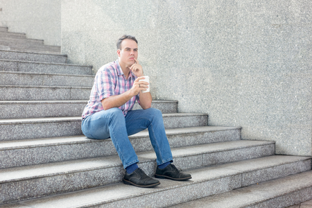 Pensive Man Sitting on City Stairway with Drink