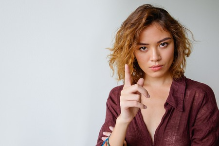 Serious young woman showing warning gesture