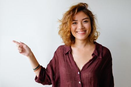Portrait of smiling young woman showing direction Stock Photo
