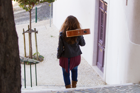 Girl Carrying Acoustic Guitar Downstairs Outdoors