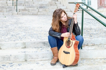 Focused Woman with Guitar Picking Song