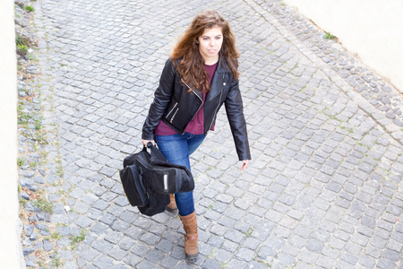 Focused Woman with Guitar Walking Down Street