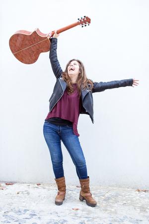 Happy Woman Raising Guitar over Head in Triumph