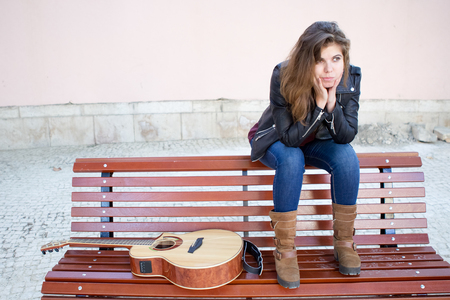 Pensive Woman with Guitar Sitting on Bench Outside