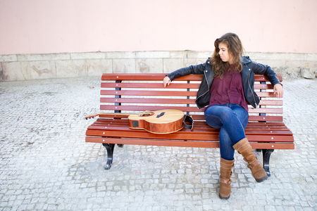 Dreamy Young Woman with Guitar on Bench Outside