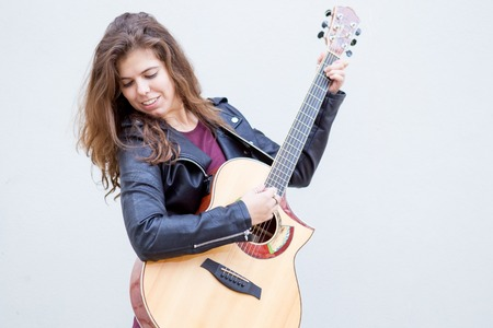 Smiling Young  Woman Playing Guitar and Looking Away