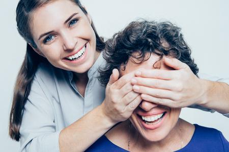 Smiling daughter making surprise for senior mother