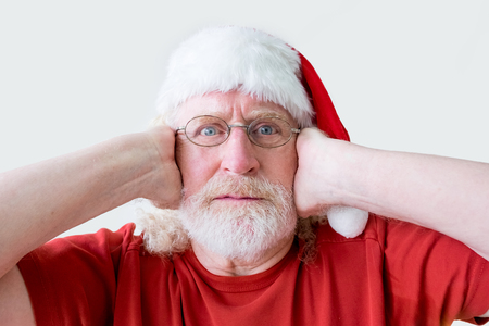 Stressed Man in Santa Hat Closing Ears with Hands Stock Photo