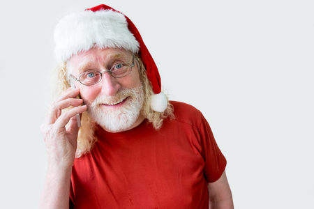 Smiling Senior Man in Santa Hat Talking by Phone Stock Photo