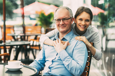 Young Woman Embracing Father and Smiling in Cafe