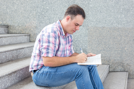 Concentrated student boy making notes in workbook