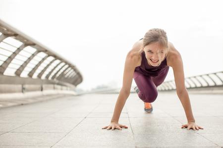 Girl Doing Mountain Climber Exercise on Bridge Stockfoto
