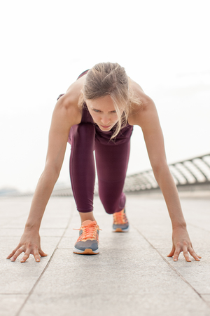 Motivated Young Woman in Starting Position on Bridge