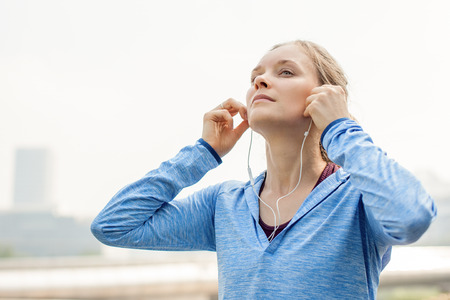 Closeup of Sporty Girl Listening to Music in City Stock Photo
