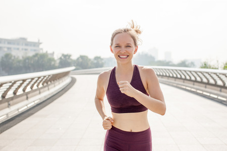 Smiling Sporty Woman Running on Bridge