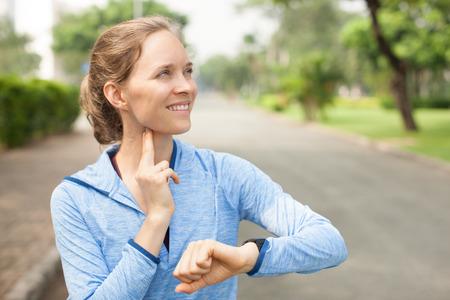 sonriente mujer deportiva que toma el pulso al aire libre